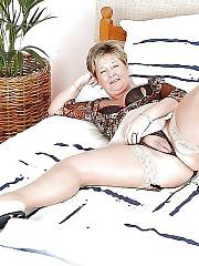 Mamma margie spreading and fondling her wet bald pussy on bed.