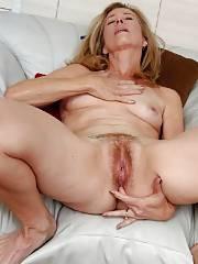 Blond mature fingering her anus