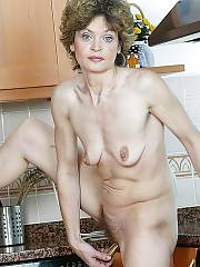 Mature hannah undresses naked and wanking her hairy pussy at home.