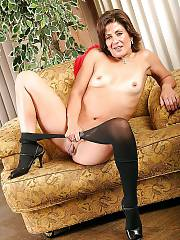 Mother in black pantyhose undresses and positions nude on couch.
