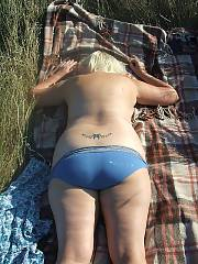 Horny mother outdoors sunning herself. vagina tattoo and piercings, what a whore!