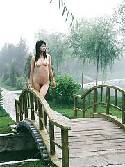 Asian babe posing naked outdoor.