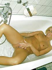 German light haired slut stroking her wet twat in the tub