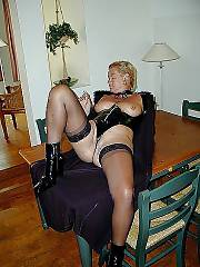 Smoking sexy light haired mom angela in black suit and stockings.