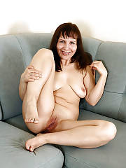 Nasty black haired mature mamma spreads and touches her wet snatch on couch.
