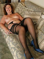 Red-haired mamma in stockings strips nude on couch.