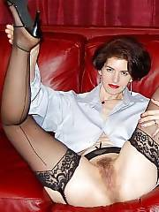 Mom in stockings spreads her twat on couch.