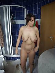 Busty nude dark haired mamma in the bathroom.