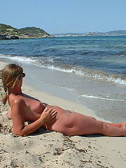 Hard body grandma out on vacation, getting naked on the warm beach and giving a hand job