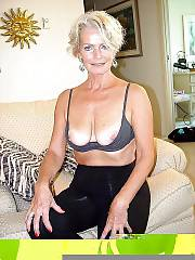 Nice light haired granny exposing boobs and spreading her cunt on couch.