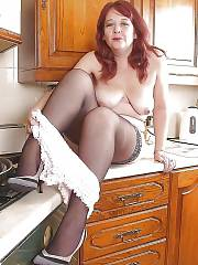 Hot amateur red-haired MILF undresses in the kitchen.