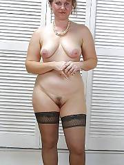 Blond MILF in stockings strips
