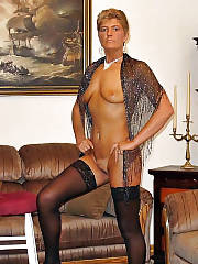 Hot MILF posing in black stockings and smoking at home.