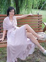 Leggy mature brunette in long party dress and high heeled sandals