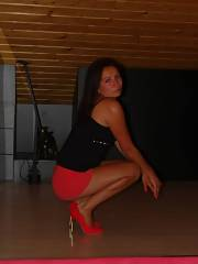 Dark hair mamma in tight short red skirt black top and red stilettos