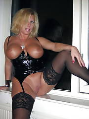 Boobed blonde mother in black at the window