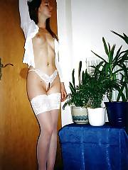 Sexy brunette slut in stockings undresses at home.