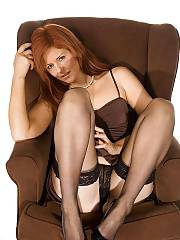 Hot red-haired MILF in stockings teasing on couch.
