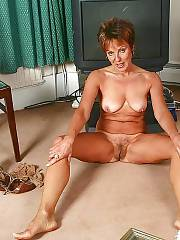 Sexy redheaded MILF posing and undresses naked.