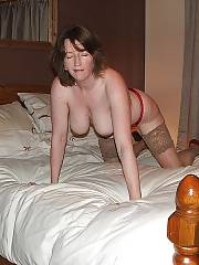 Mature brunette mother strips nude on bed.